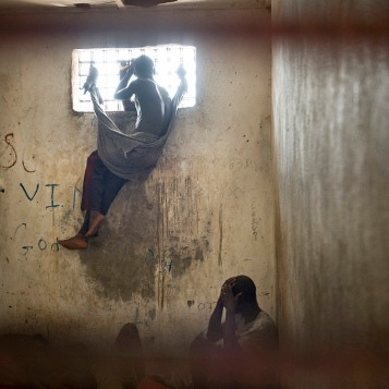 A Nimba county prison inmate looks through the window of a cell during a tour of the overcrowded facility by Henrietta Mensa-Bonsu, Deputy Special Representative of the Secretary-General for the United Nations Mission in Liberia (UNMIL) for Rule of Law- Photo ID 234114. 02/12/2008. Sanniquellie, Liberia. UN Photo/Christopher Herwig via flickrCC